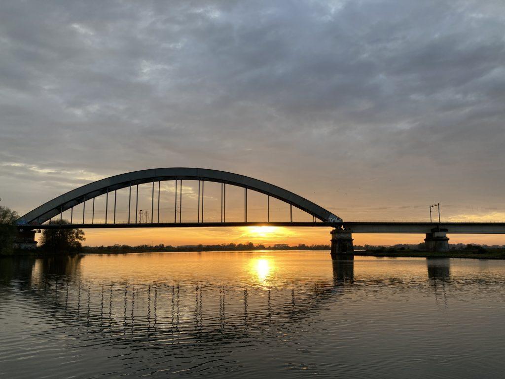 Spoorbrug over de lek bij zonsondergang